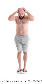 Overweight man measuring his weight using scales on white background