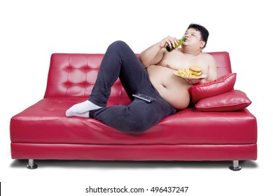 Overweight man reclining on couch and holding junk food while drinking fresh beer  with watching tv, isolated on white the background