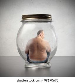 Overweight man sitting in a jar