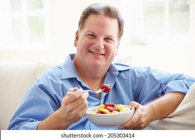 Overweight Man Sitting On Sofa Eating Bowl Of Fresh Fruit