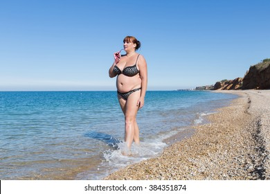 Overweight middle aged woman at the sea. Overweight woman in swimwear walking along seashore