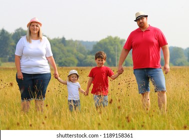 Overweight parents with her children walking together. Family enjoying life on countryside.