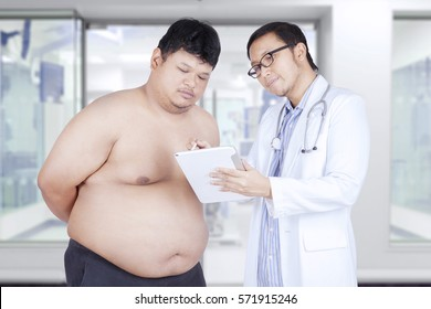 Overweight patient and his doctor looking at a test result on a digital tablet in the hospital