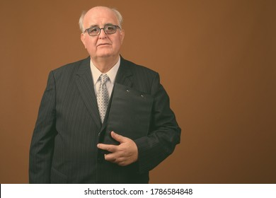 Overweight senior businessman wearing eyeglasses against brown background