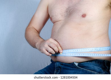 Overweight shirtless caucasian man measuring his stomach