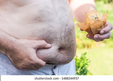 Overweight white male holding his belly fat with one hand and a cake with another hand. Obesity concept.