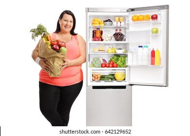 Overweight woman with a bag of groceries leaning on an open refrigerator isolated on white background