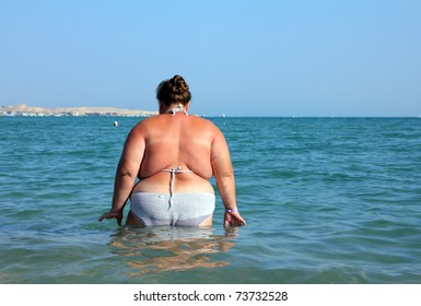 overweight woman bath in sea - rear view