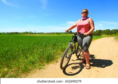 Overweight woman and bicycle. Active people enjoying summer holidays on countryside.
