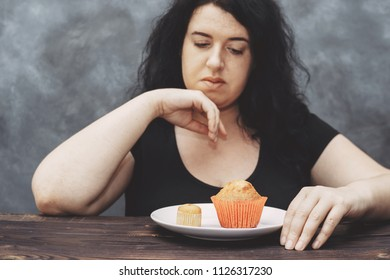 Overweight woman choosing between little and big muffins. Sense of proportion, cheat meal, portion size, self control, dieting, sugar addiction and weight loss