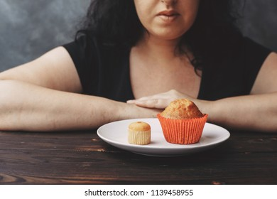 Overweight woman choosing between little and big muffins. Sense of proportion, self control, dieting, sugar addiction and weight loss