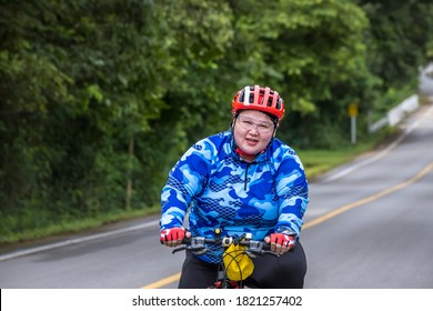 Overweight Woman cyclist in mountain. Biking travel tour on rural road at Suan Phueng district, Ratchaburi, Thailand.