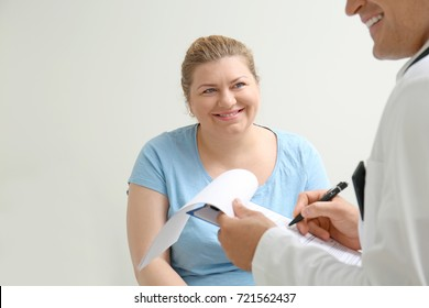 Overweight woman discussing test results with doctor in hospital