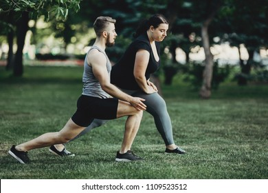 Overweight woman doing lunges exercise with trainer support. Personal fitness instructor controlling his client street workout. Fitness, sport, training, weight loss, teamwork and lifestyle concept.