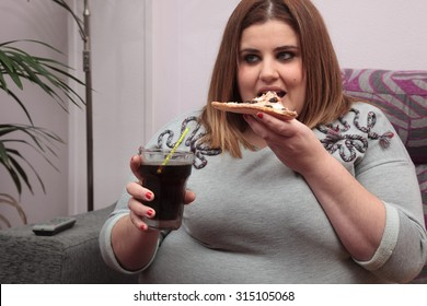Overweight woman eating pizza on the couch