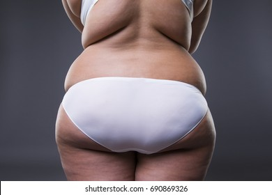 Overweight woman with fat legs and buttocks, obesity female body on gray background