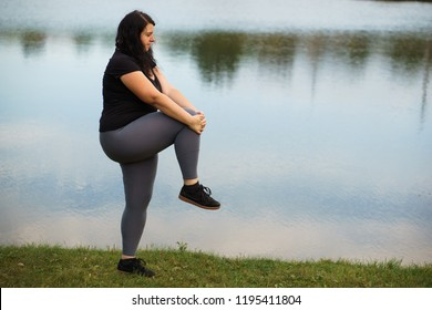 Overweight woman get ready for jogging in the park. Female runner stretching legs and warming up outdoors. Weight loss, sports, healthy lifestyle