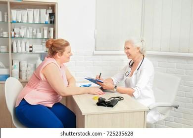 医院で診察を受けている太り過ぎの女性