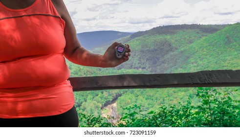 Overweight woman holding a 10,000 steps pedometer on a hiking trail with a beautiful view