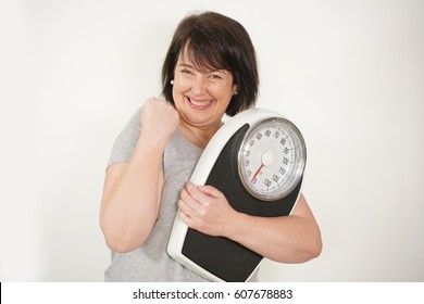 Overweight woman holding scale on white background