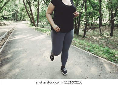 Overweight woman losing weight running in park. Street workout, fitness, sport, healthy lifestyle concept.