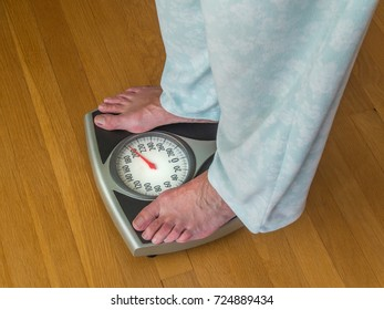 Overweight woman in pajamas weighing herself