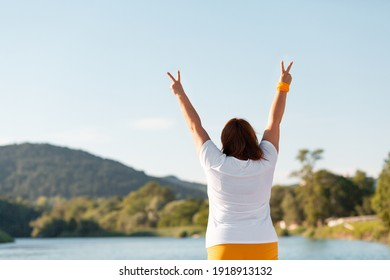 The overweight woman raised the top of her hand and pointed her fingers at the victory sign. The view from the back. Copy space.