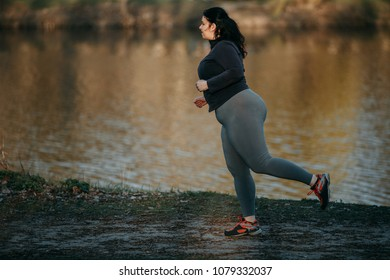 Overweight woman runner go jogging outdoors. Weight loss, sports, healthy lifestyle