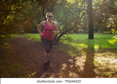 Overweight woman running in the park . Weight loss concept.