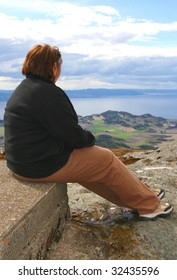Overweight woman sitting on a mountain