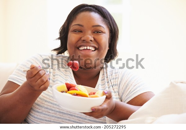 Overweight Woman Sitting On Sofa Eating Bowl Of Fresh Fruit