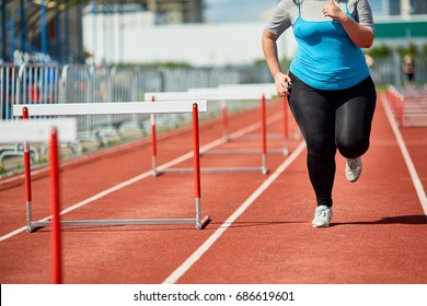 Overweight woman in sportswear running along one of race tracks at stadium