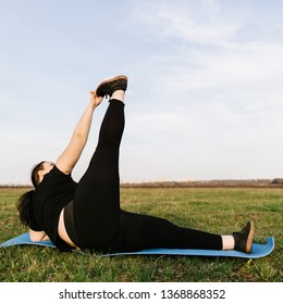 Overweight woman in sportswear training legs on yoga mat in open air on the meadow, copy space. Healthy lifestyle, sport, weight losing, activity concept