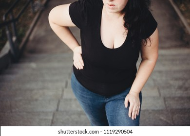Overweight woman suffering from breathe shortness stepping on stairs. Excess weight, heart problems, health care and medical concept