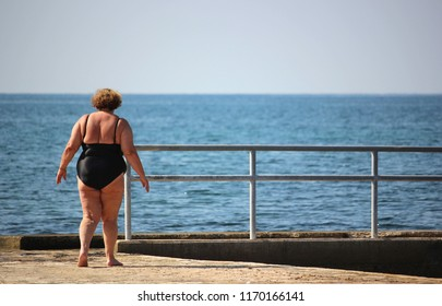 Overweight woman in swimsuit standing by the sea on a sunny day