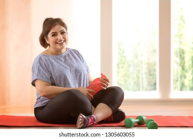 Overweight woman taking a break from exercising
