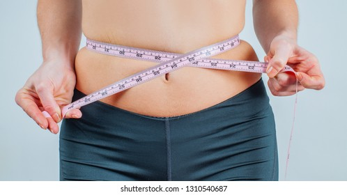 Overweight woman with tape measure around waist. Woman measuring her waistline fat tummy