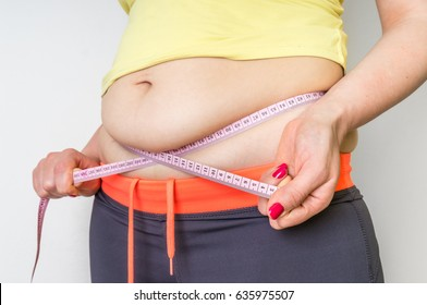 Overweight woman with tape is measuring fat on belly - obesity concept