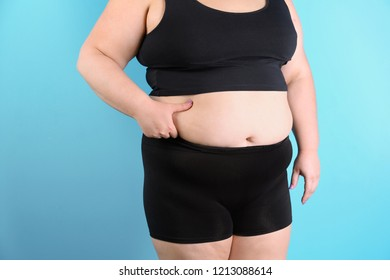 Overweight woman touching belly fat before weight loss on color background