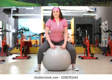 Overweight woman training with fitball in gym