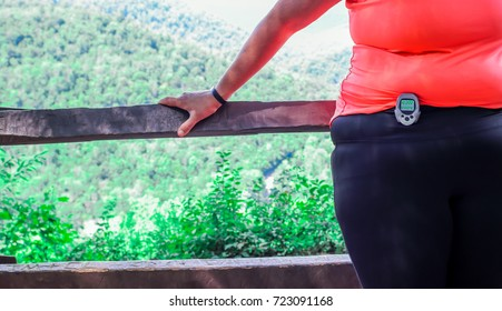 Overweight woman walking with a 10,000 steps  pedometer in the woods with a beautiful view