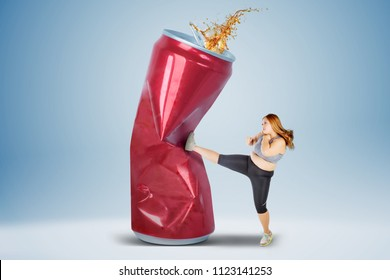 Overweight woman wearing sportswear while refusing coke drink and kicking a can