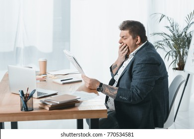 overweight yawning businessman in suit reading newspaper at workplace