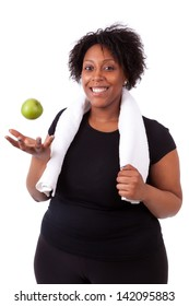 Overweight young black woman holding an apple, isolated on white background - African people