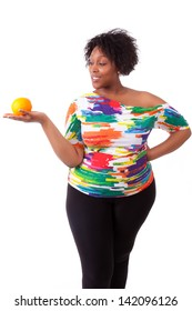 Overweight young black woman holding an orange, isolated on white background - African people