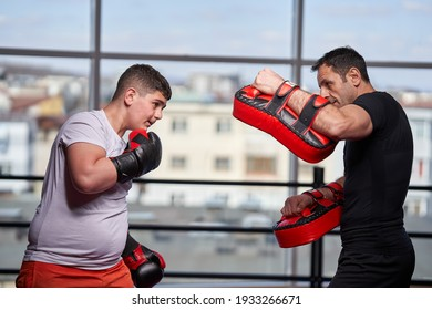 Overweight young kickboxer hitting mitts with his coach