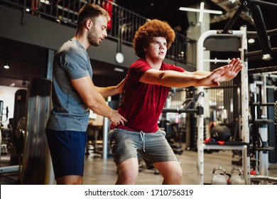 Overweight young man exercising gym with personal trainer