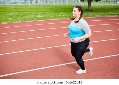 Overweight young woman in activewear trying to get fit and running on stadium