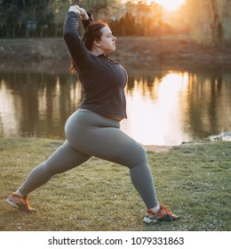 Overweight young woman doing yoga in morning park. Healthy lifestyle, sport, weight losing, relaxation concept