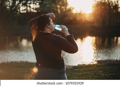 Overweight young woman drinking water after jogging outdoors. Weight losing, sports, healthy lifestyle